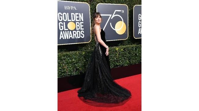Aktris Dakota Johnson tampil beda dengan gaun Gucci, serta gemerlap perhiasan di bagian pinggang dan belakang gaun. (AFP PHOTO / VALERIE MACON)