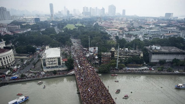 Jutaan umat Katolik ini bukan hanya datang dari Manila, namun juga seluruh penjuru Filipina. Patung Black Nazarene yang menggambarkan Yesus tengah memapah salib hitam diyakini banyak mendatangkan keajaiban dan keberkahan.(AFP PHOTO / NOEL CELIS)