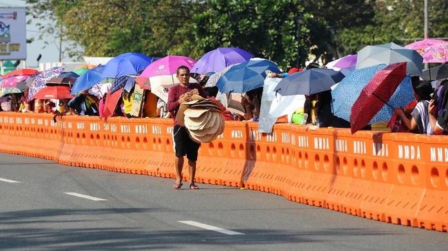 Dalam Festival Black Nazarene, patung yang bersemayam dalam sebuah lokasi di kawasan kuno Intramuros Manila, dipindahkan dengan arak-arakan keGereja Quiapo. Tradisi ini kerap dilakukan oleh penganut Katolik sebagai ungkapan penghormatan pada relik suci.(AFP PHOTO / Ted ALJIBE)