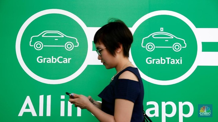 A woman passes a Grab signage at their office in Singapore September 23, 2016. REUTERS/Edgar Su  - RTSP2AJ