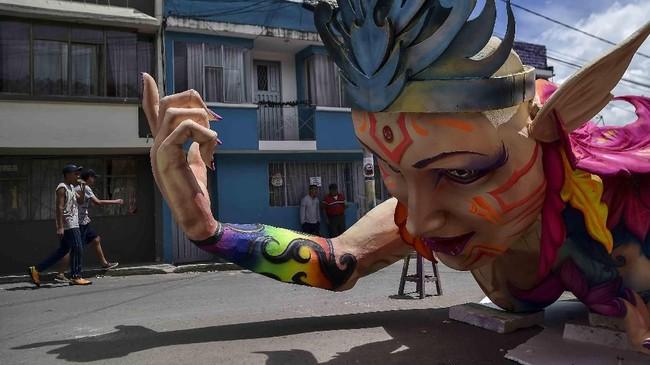 <p>Seorang pria berjalan di tengah-tengah perayaan Karnaval Hitam dan Putih di barat daya Kolombia. Lebih dari 10 ribu seniman, pengrajin, serta pengunjung ambil bagian dalam festival yang semula merupakan bentuk ekspresi budaya suku Andean, Amazon, dan Pasifik. (AFP/Luis Robayo)</p>
