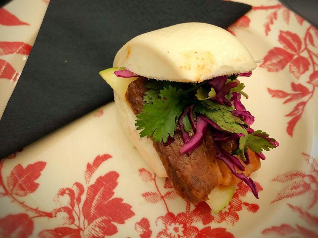 Ada juga roti bun warna putih yang disajikan bersama irisan pork belly dan sayuran segar. Foto: Instagram