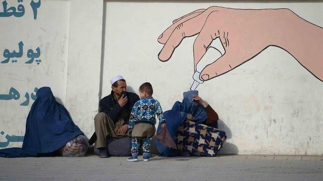 <p>Perempuan Afghanistan yang mengenakan burka, seorang pria, dan seorang anak, duduk bersama di tepi jalan kota Mazar-i-Sharif. (AFP/Farshad Usyan)</p>