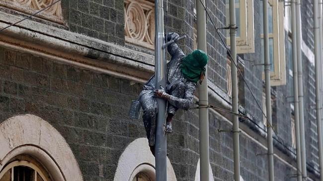 <p>Seorang pekerja mengecat tiang lampu di jalanan Mumbai, India. (Reuters/Shailesh Andrade)</p>