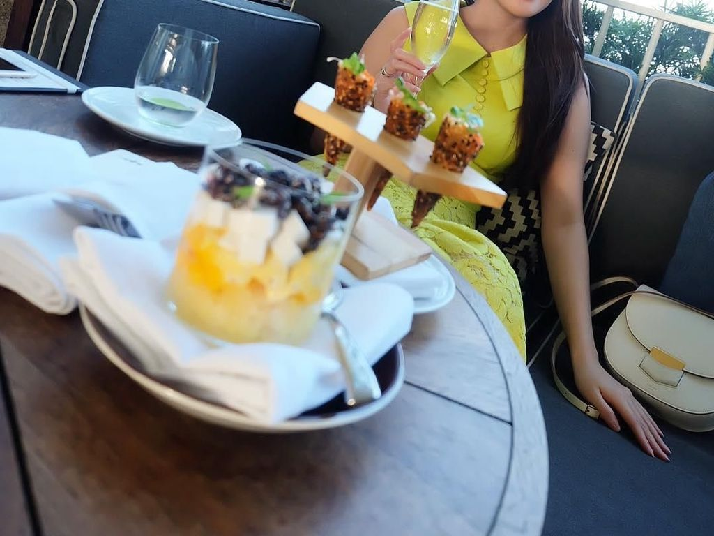 Dengan mengenakan dress berwarna kuning, Shandy dengan rambut panjangnya berfoto dengan minuman dan aneka dessert. Foto: Instagram shandyaulia