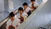 Perempuan-perempuan Jepang yang mengenakan kimono menggunakan eskalator di stasiun bawah tanah Tokyo, Jepang, setelah mengikuti perayaan Akil Baligh. (Reuters/Kim Kyung-Hoon)