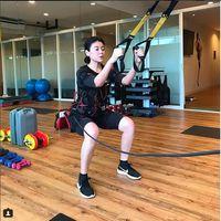 Dalam foto ini, Sigi Wimala melakukan variasi squat lainnya yang menggunakan alat bantu, yakni TRX squat. (Foto: Instagram/sigiwimala)