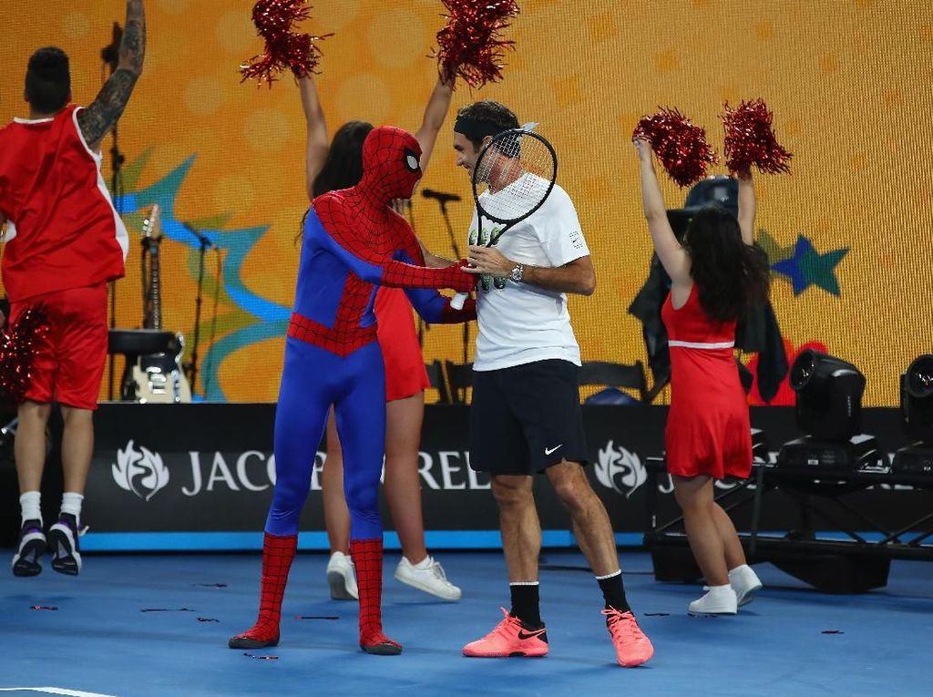 Federer sempat mencoba untuk meminjamkan raketnya kepada Spiderman. Tapi sepertinya Peter Parker tak percaya diri untuk mengayun raket. Foto: Clive Brunskill/Getty Images