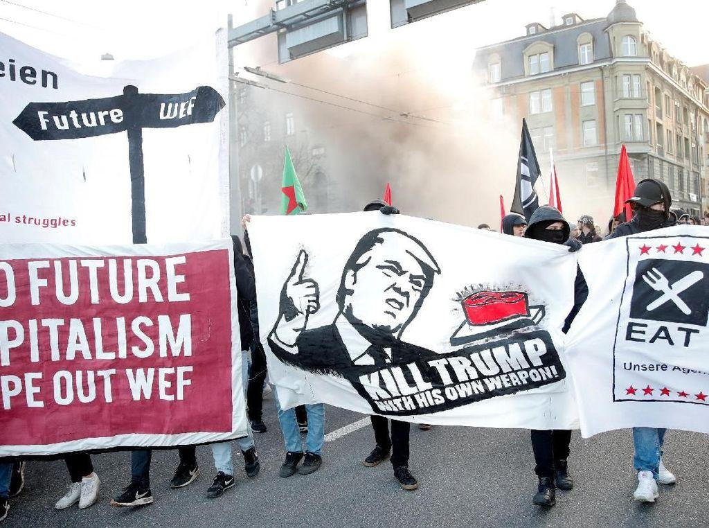 """Massa membawa sejumlah papan dan spanduk yang bertuliskan di antaranya Eat the rich and Fight WEF, dan """"Kill Trump"""". (Foto: Dok. REUTERS/Arnd Wiegmann)"""