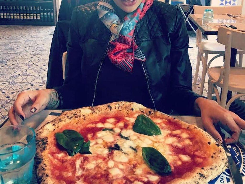 Bertandang ke Italia, Niki tak melewatkan pizza lezatnya. Seloyang pizza Italia sudah ada dihadapannya. Dengan wajah tak sabar melahap, Niki terlihat fokus memandangi pizza. Foto: Instagram @nikitamirzanimawardi_17