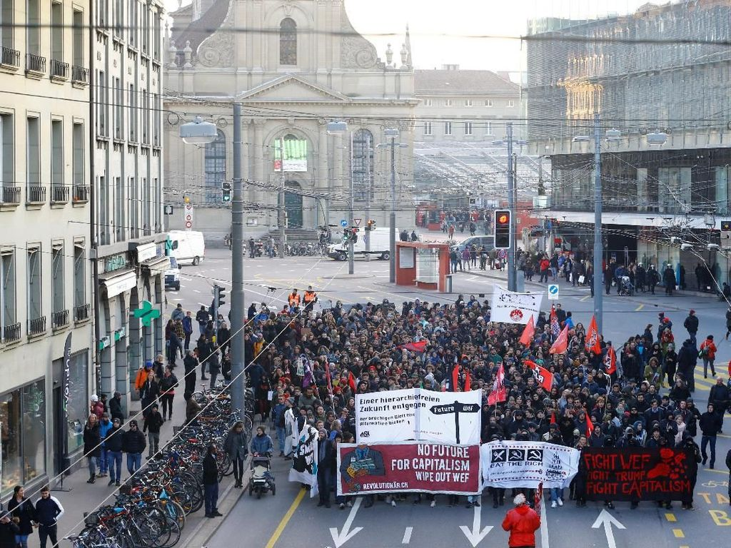 Massa anti-kapitalis menggelar long march di Bern, Swiss, pada Sabtu (14/1). (Foto: Dok. REUTERS/Arnd Wiegmann)