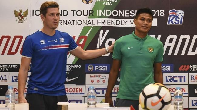 Bek Timnas Indonesia Fachrudin Aryanto (kanan) foto bersama kapten timnas Islandia Olagur Ingi Skulason saat konferensi pers jelang laga. (ANTARA FOTO/Hafidz Mubarak)