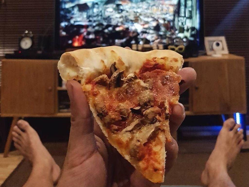 Menikmati pizza sambil nonton jadi salah satu ritual bersantai bapak satu anak ini. Foto: Instagram @riodewanto