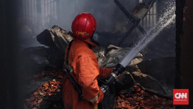 Petugas berupaya menuntaskan pemadaman sehingga tak muncul lagi bara api yang bisa memicu kebakaran kembali. (CNN Indonesia/Hesti Rika)