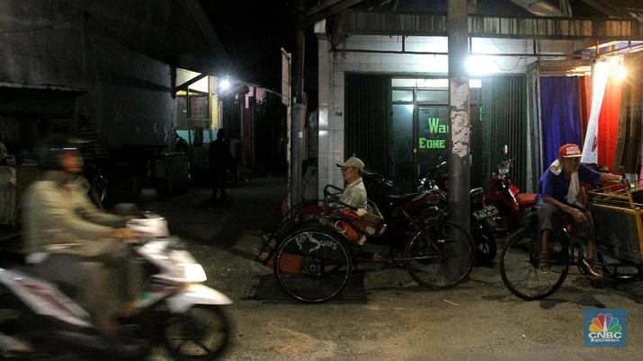Seorang pengayuh becak mengangkut penumpang di kawasan Pasar Warakas, Tanjung Priok, Jakarta, Selasa (16/1/2018) malam. Gubernur DKI Jakarta Anies Baswedan mengatakan untuk merealisasikan wacana pengoperasian becak akan disusun lebih dulu aturannya. Dalam aturan yang akan dibuat, tertuang ketentuan seperti zona pengoperasian becak, sampai sanksi bila terjadi pelanggaran.