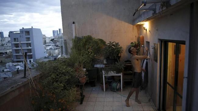 Emanuel Cohen (36) tampak sedang membersihkan diri di salah satu atap gedung di foto ini. Dia juga menggunakannya sebagai taman kecil untuk mengembangkan tumbuh-tumbuhan herbal dan sayuran. (REUTERS/Corinna Kern)