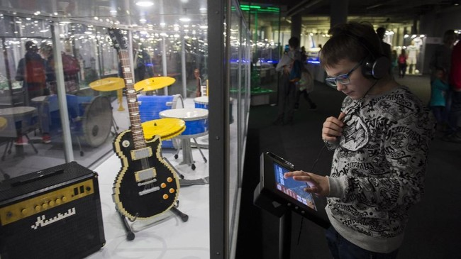 Seorang anak memeriksa instalasi layar sentuh untuk alat musik, yang terbuat dari mainan LEGO. (Anadolu Agency/Omar Marques)