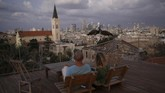 Arieh Ramot dan Orna Ramot adalah dua dari sekian banyak warga Tel Aviv yang menjadikan atap gedung sebagai tempat rekreasi. Dalam foto ini, mereka tampak memandangi burung yang kerap datang ke sana setelah diberi makan oleh tetangga. (REUTERS/Corinna Kern)