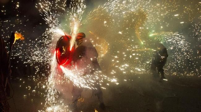 Perayaan Correfocs juga diyakini muncul sebagai aksi spontaniatas para penonton dan peserta festival tradisional Ball de Diables atau 'Tarian Iblis'.(AFP PHOTO / JAIME REINA)