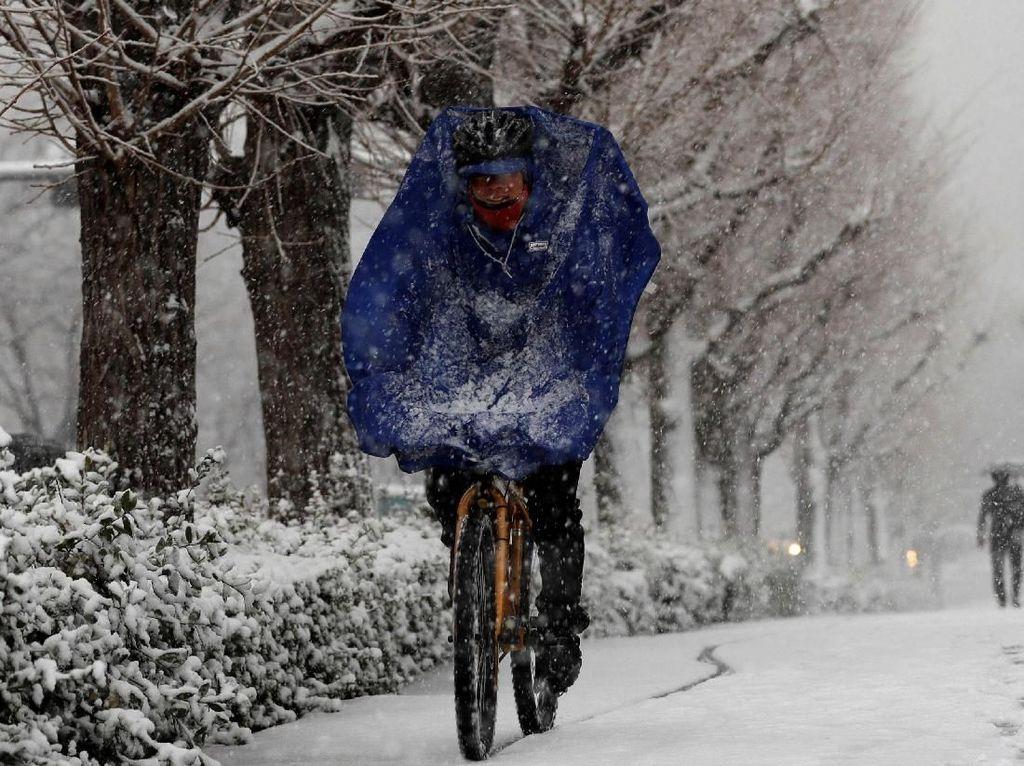 Pria ini pun tetap bersepeda saat hujan salju yang deras.
