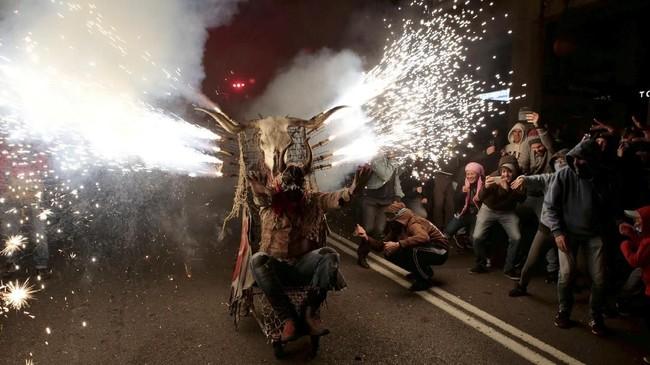 Perayaan Correfocs dilakukan dengan mengenakan kostum. Para peserta mengenakan kostum berbentuk iblis yang melambangkan kejahatan. (REUTERS/Enrique Calvo)