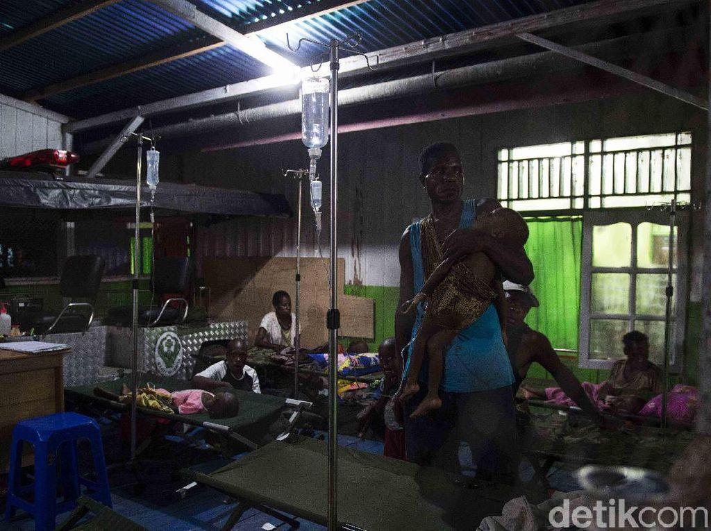 Warga menggendong anaknya saat menjalani perawatan, di Rumah Sakit Umum Daerah (RSUD) Agats, Kabupaten Asmat, Papua, Senin (22/1). M Agung Rajasa/Antara Foto.