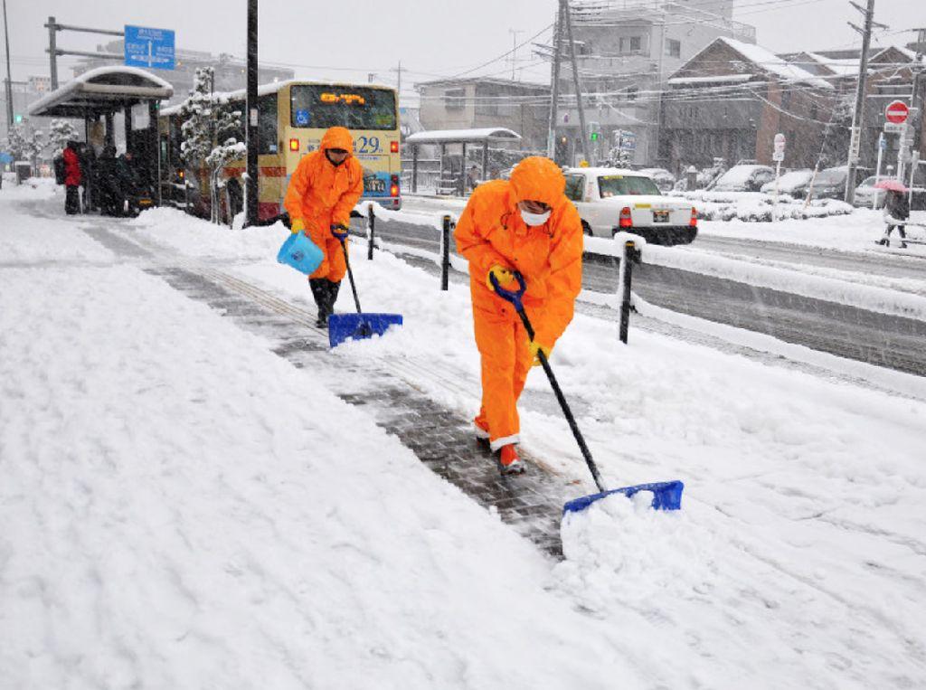 Pekerja kota membersihkan salju tebal yang ada di depan gedung pemerintah daerah di Machida, Tokyo, 22 Januari 2018. (Foto: Dok. The Mainichi)