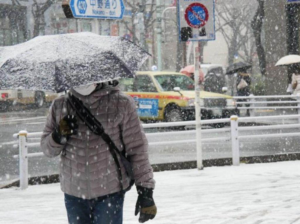 Seorang pria berjalan di jalanan tertutup salju di Nakano Ward, Tokyo, 22 Januari 2018. Kemarin, seperti dilansir Reuters, layanan kereta api setempat terpaksa dibatalkan akibat cuaca buruk. (Foto: Dok. The Mainichi)