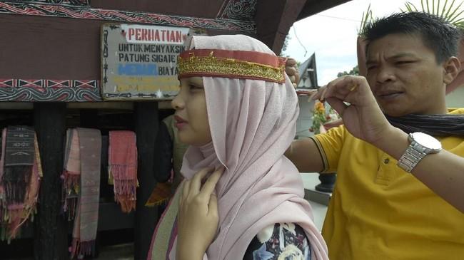 Turisasal Malaysia memakai ikat kepala wanita khas Batak Toba sebelum tampil menari Tortor bersama Sigale Gale.