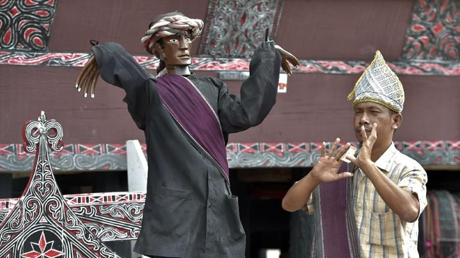 Turis terlihat menari Tortor di depan patung Sigale Gale.