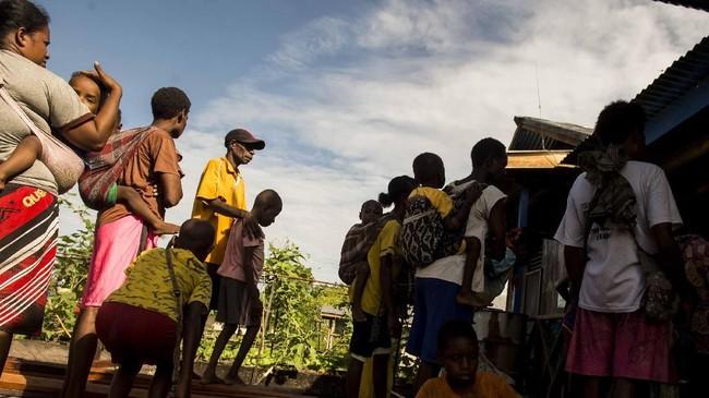 Keuskupan setempat juga membantu warga. Tampak Warga mengantre pembagian bantuan kemanusian di Distrik Jetsy, Kabupaten Asmat, yang dikoordinir oleh tim Keuskupan Agats. (ANTARA FOTO/M Agung Rajasa/ama/18)