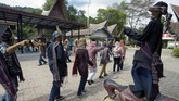 Sejumlah turis menari membentuk lingkaran. Diiringi musik Sordan dan Gondang Sabangunan, mereka menari Tortor di depan Sigale Gale.