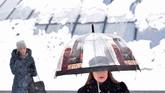 Seorang perempuan berjalan menggunakan payung di pusat kota Kiev, Ukraina, ketika terjadi hujan salju yang tebal. (AFP/ Sergei SUPINSKY)