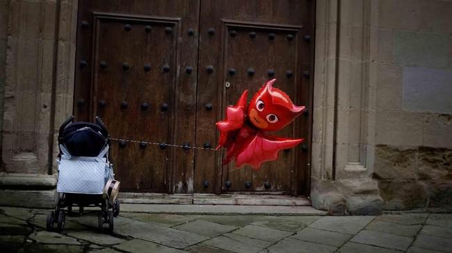 Balon merah diikatkan pada kereta dorong anak ketika festival Tamborrada di hari San Sebastian berlangsung. Saat festival itu, orang-orang berpakaian seperti prajurit Napoleon dan tampil dalam ajang bermain drum 24 jam. Festival ini berlangsung di kota San Sebastian, Spanyol. (REUTERS/Vincent West)