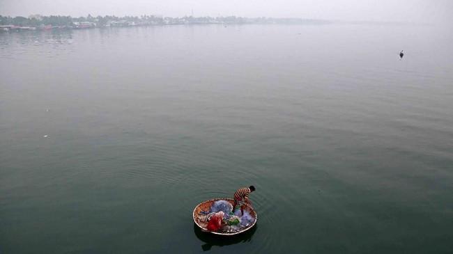 Seorang nelayan dan istrinya menangkap ikan di Danau Vembanad, di kota Kochi, India. (REUTERS/Sivaram)