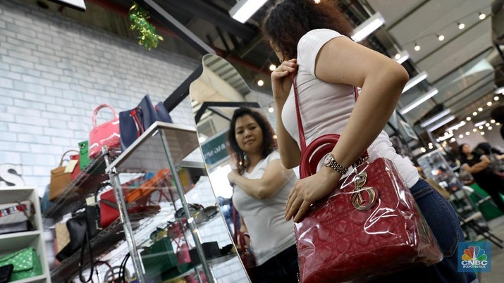 Pengunjung melihat tas yang di jual di bazar post market, di Lippo Puri Indah,  Jakarta Barat,  Jumat (2/2/2018). Bazar yang berlangsung selama 1-4 februari ini menjual barang-barang merk ternama yang harganya mulai dari jutaan hingga puluhan juta rupiah. Tak sedikit orang yang berkunjung ke lokasi tersebut, kebanyakan dari mereka yang datang kalangan kelas menengah atas dan kolektor tas tas mewah. (CNBC Indonesia/Muhammad Sabki)