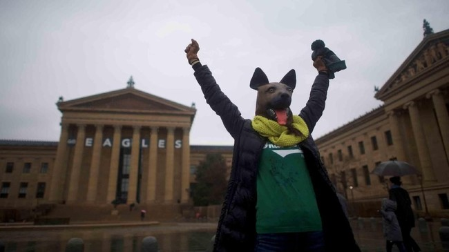 Seseorang mengenakan topeng anjing sebagai penanda ia pendukung tim underdog (kuda hitam). Ia berada di luar Museum Seni Philadelphia sebelum pertandingan Super Bowl LII antara Philadelphia Eagles dan New England Patriots di Philadelphia, Pennsylvania, AS. (REUTERS/Mark Makela)