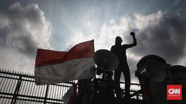 Seorang orator Aliansi Masyarakat Sipil berdiri di atas mobil komando dengan pengeras suara, dan bendera Merah Putih berkibar di sisinya. (CNN Indonesia/Andry Novelino)
