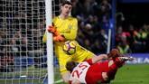 Thibaut Courtois menggagalkan upaya bek West Bromwich Albion, Craig Dawson. Kiper Chelsea itu kerap membuat para pemain lawan frustrasi. (REUTERS/Eddie Keogh)