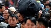 <p>Kerumunan manusia memanggul koper dan kardus mi instan terlihat berjejalan memasuki stasiun di Beijing, menunggu kereta yang akan membawa mereka ke kampung halaman. (China Daily via Reuters)</p>