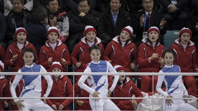 Mereka tetap berkonsentrasi di tengah terpaan jepretan kamera penonton yang antusias menyaksikan aksi pemandu sorak Korut untuk pertama kalinya. (AFP Photo/Ed Jones)
