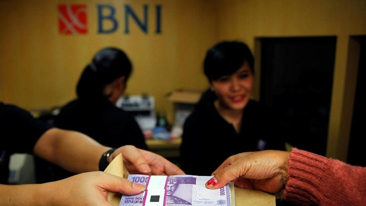 FILE PHOTO: A woman holds Indonesian rupiah banknotes at a Bank Negara Indonesia (BNI) mobile bank in Jakarta July 15, 2013.   REUTERS/Beawiharta/File Photo