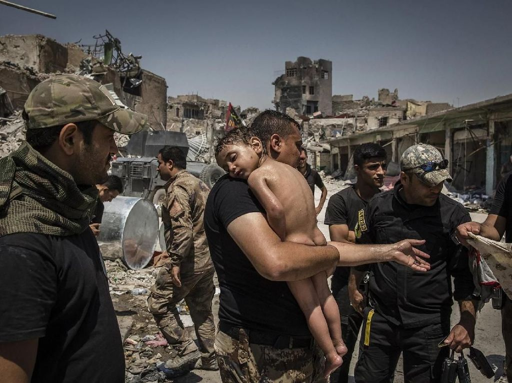 Seorang anak laki-laki yang akan dibawa keluar dari Kota Tua Mosul oleh sorang pria tentara Irak untuk dirawat - karya Ivor Prickett/New Yorks Times.. Foto: World Press Photo/The Washington Post