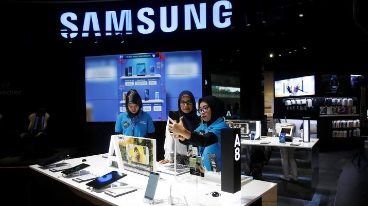 A salesperson (R) serves a customer at a Samsung phone showroom in Jakarta, Indonesia, January 26, 2018. REUTERS/Beawiharta