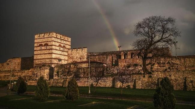 Pelangi terlihat di tembok Byzantium yang bersejarah, setelah hujan badai menerpa Distrik Topkapi, Istanbul, Turki. (AFP PHOTO / OZAN KOSE)