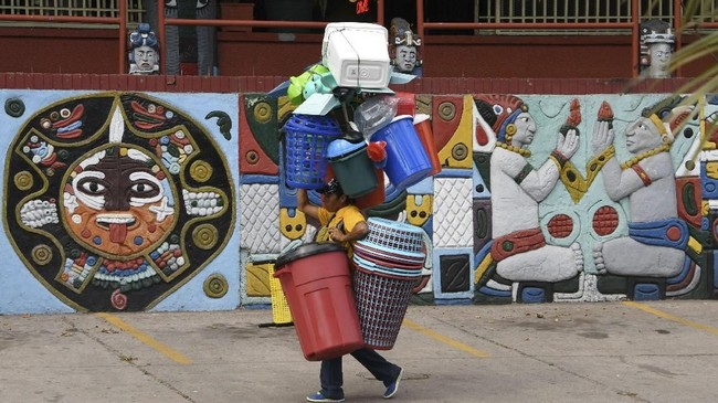 Seorang penjual membawa perabot plastik di jalanan kota Tegucigalpa, Honduras. (AFP PHOTO / ORLANDO SIERRA)