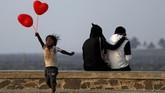 Seorang anak melompat setelah berusaha menjajakan balon berbentuk hati pada pasangan yang sedang berdusaan di hari Valentine di Mumbai, India. (REUTERS/Francis Mascarenhas)