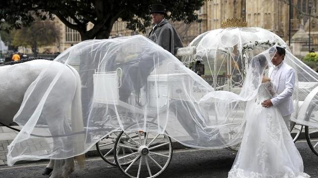 Sepasang pengantin berdiri dekat kereta kuda di luar Istana Westminster di London Tengah, Inggris. (REUTERS/Peter Nicholls)