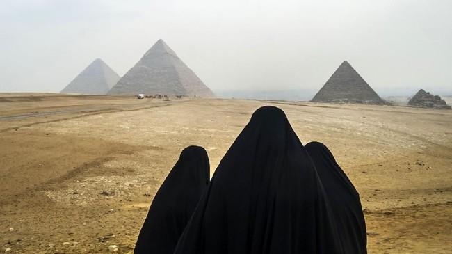 Wisatawan perempuan mengenakan kerudung hitam menatap Piramida Giza dari kejauhan. Mereka duduk di dataran tinggi Giza yang terletak di luar kota Cairo, Mesir. (AFP PHOTO / KHALED DESOUKI)