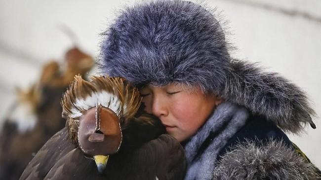 Seorang pemburu muda beristirahat dekat elang emas yang sudah dijinakkannya. Ia sedang mengikuti acara tahunan kompetisi berburu di Almaty, Kazakhstan. (REUTERS/Shamil Zhumatov)